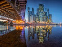 Россия. Москва-сити. Reflection of Moscow City and Dorogomilovsky Bridge in the Moscow River in the evening. Фото sobioru - Depositphotos