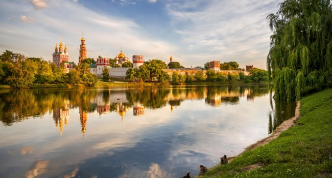 Россия. Москва. Панорама Новодевичьего монастыря. Novodevichy Convent at sunset with reflection in the lake and the ducks on the shore. Фото yulenochekk-