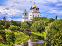 Россия. Псковский кремль. The golden dome of Trinity Church and towers of Pskov Kremlin (Krom) reflecting in the river, Pskov, Russia. Фото Xantana - Depositphotos