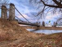Храмы Пскова. Suspension bridge connecting the banks of the river and the island in the river, in the town Ostrov of Pskov region. Фото yulenochekk - Depositphotos