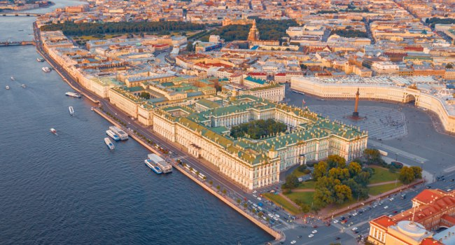 Россия. Санкт-Петербург. Aerial view of Palace Square Hermitage Winter Palace and embankment of the Neva River in the evening at sunset. Фото aapsky - Depositphotos