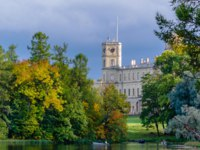 Old hunting castle in autumn Gatchina Palace Park on the shore of Silver lake on the background of blue sky and clouds. Фото vagrig - Depositphotos