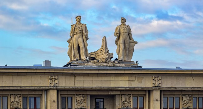 Санкт-Петербург. Петровская набережная. Statues on roof of the residential house of the military seamen on Petrovskaya embankment, 8. Фото Igor-SPb - Depositphotos
