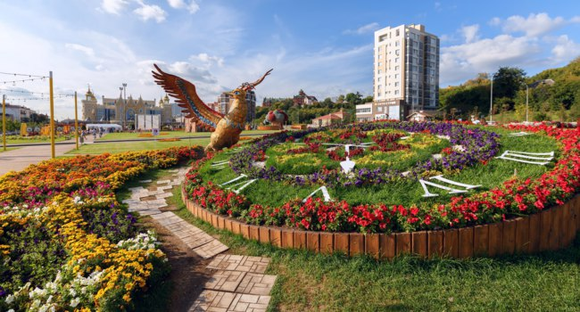 Flower Festival on the Square in front of Ekiyat Puppet Theatre. View of Flower clock and Firebird sculpture. Kazan, Republic of Tatarstan. Фото Balakate-Depositphotos