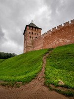 Великий Новгород. Новгородский детинец. View of red brick wall of ancient fortress with green meadows in front, Velikiy Novgorod. Фото asokolov160585 - Deposit