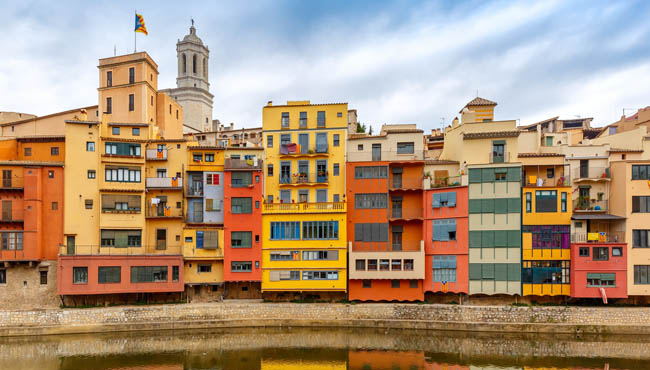 Испания. Каталония. Жирона. Colorful yellow, red and orange houses with the Catalan flag reflected in river Onyar, in Girona. Фото olgacov - Depositphotos