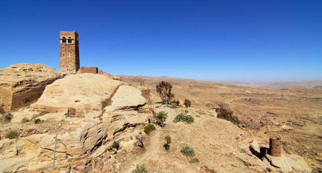 Йемен. Landscape of mountain Yemen in Eastern Haraz. Old fortress against blue sky. View from Thula village. Фото znm666 - Depositphotos