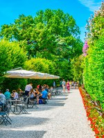 Италия. Озеро Маджоре. People are sitting in a cafe inside of the gardens of the Borromeo Palace on Isola Bella, Italy. Фото Dudlajzov-Depositphotos
