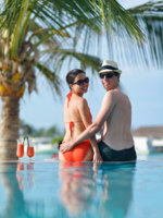 Мальдивы. Maldives. Happy young couple relax and take fresh drink. Фото benis arapovic - Depositphotos